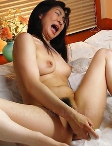 Emiko Koike pleases herself on bed